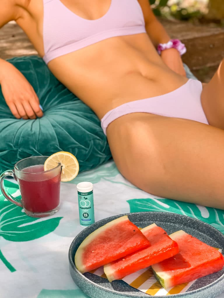 Woman with flat stomach relaxing with Superfood Tabs drink